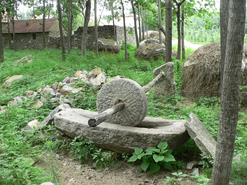 Millstone, with a stone house and wall in the background