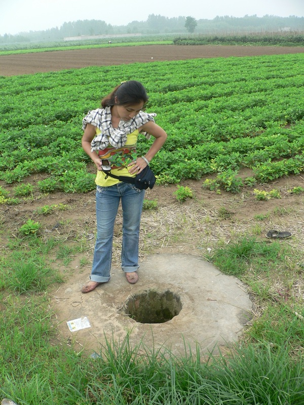 Ah Feng looking down a well in the middle of the fields