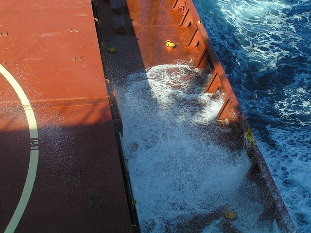 More breakers splashing on the ship's main deck