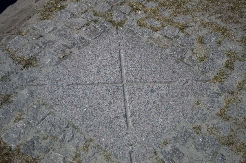 The confluence point is marked by a cross in a concrete slab