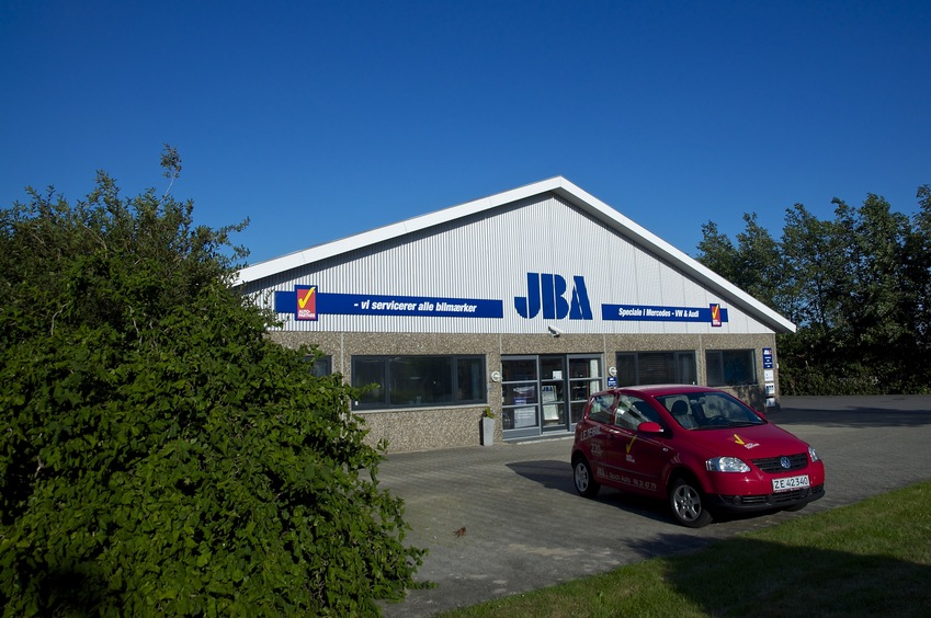 "The front of the JBA (""J. Block Auto"") repair business.  The confluence point lies just inside the left-hand wall (hidden behind the bush)"