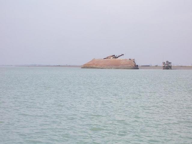 Looking west from 30N 48E, another ship wreck is in front of al-Fāw peninsula, Umm Qasr is on the distant horizon