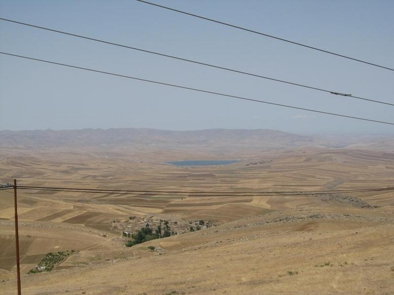 The view from higher up: farmland, villages, and a reservoir lake