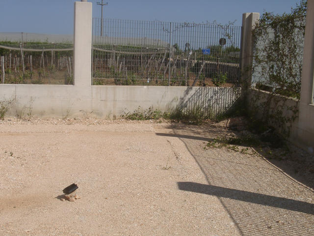 Gravel surface in a partly finished compound with wineyard