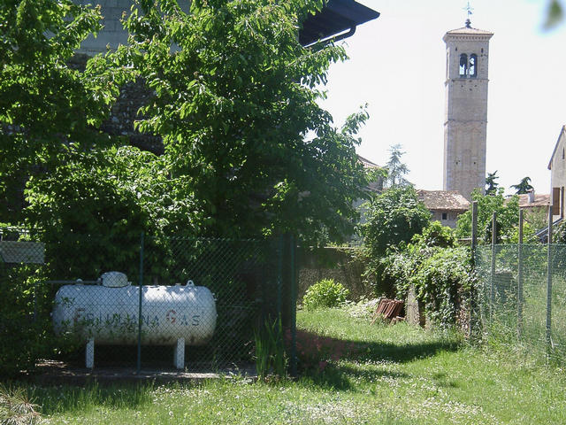 The confluence point is at the corner of the house, behind the gas tank (seen from the east). Background: church of San Lorenzo