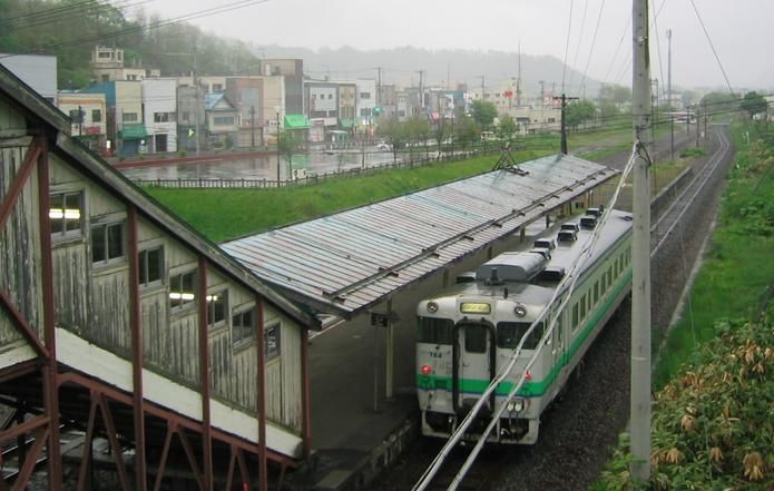 Shimizuzawa station with local train in foreground and town in background.