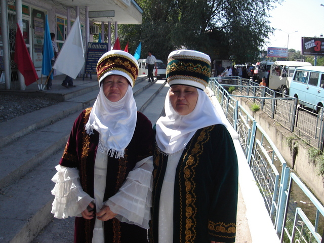 two kyrgysz women in traditionell dress attending the event