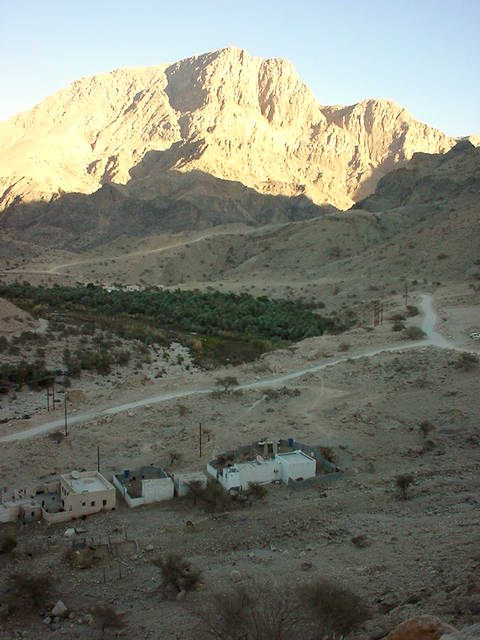 Jabal Thanab with the winding road to the wādiy al-`Arabiyyīn. Also: Date palm groves.