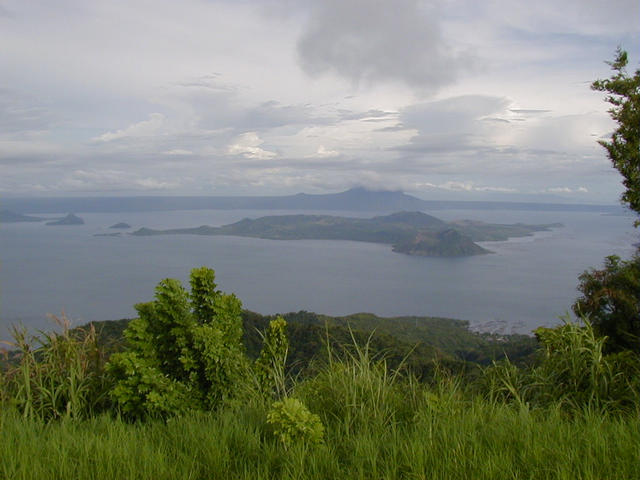 The confluence sits on the backside of Volcano Island (center of photo) in Taal Lake. View is SSE from the town of Tagatay on the northern rim of the pre-historic Taal Volcano. The Southern rim and Mt. Maculot (shrouded in clouds) are in the background.