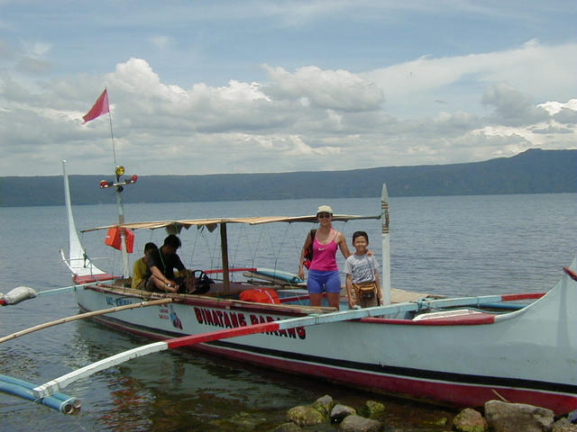 "Olma and Kristoff on the banca before our swim. This is a stylized lake version of the typical ""outrigger"" type boat. Larger and more rugged ocean versions are used throughout the Philippine's 7,000 islands."