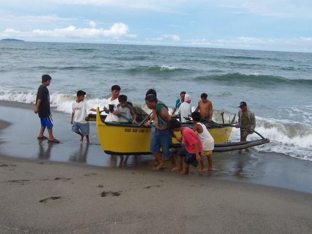 All hands on deck to lift newly landed boat to escape the next wave