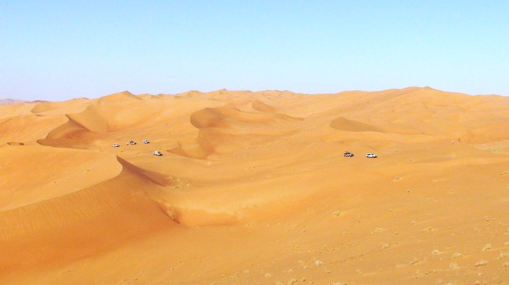 Six vehicles navigating through the dunes