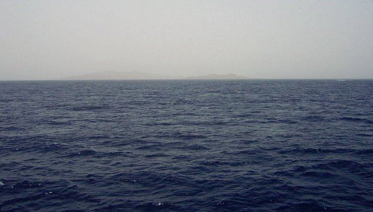 View looking SE at 25N 37E with reef break waves and distant Hasāniyy and Libāna Islands