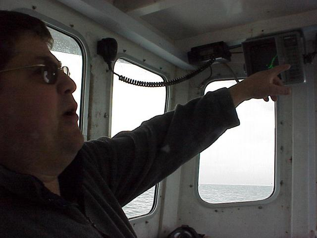 Dave Turner, commercial fisherman and captain of the Sarah Louisa, points out some of the electronic features of the boat.