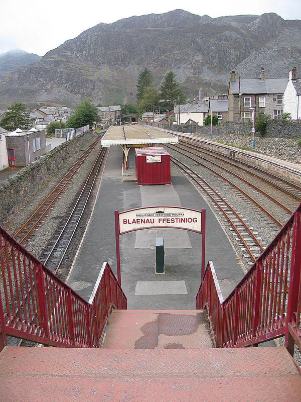 Blaenau Ffestiniog railway station with both narrow guage and regular tracks.  Moelwyn Mountains in the background.