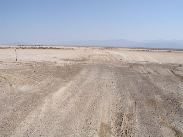 A mile north of 36N 116W, the nearby road crosses a dry lakebed.