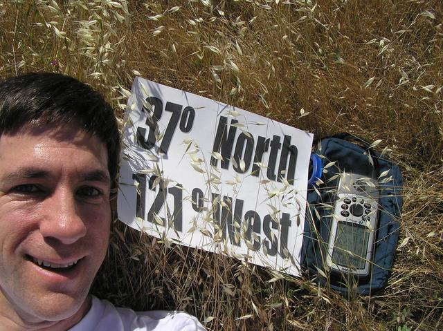 Joseph Kerski lying in California's golden fields on 37 North 121 West.