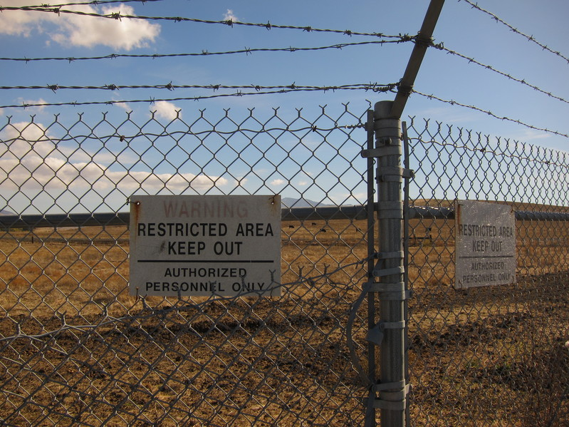 Restricted area notices on the chain link fence