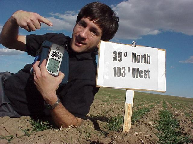 Joseph Kerski, lying in the field, at the confluence site.