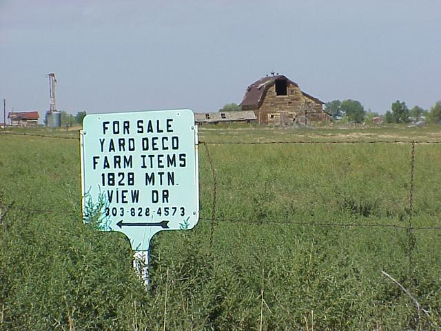 Signs of the times...selling farm items and an abandoned barn, looking north from the confluence.