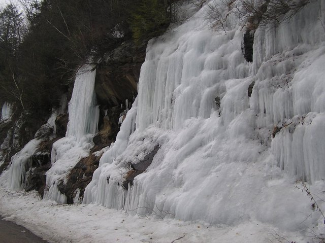 Stalactites of ice flowing from roadside ledges