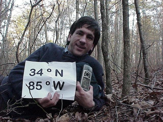 Joseph Kerski at 34 North 85 West, lying in a Georgia forest.