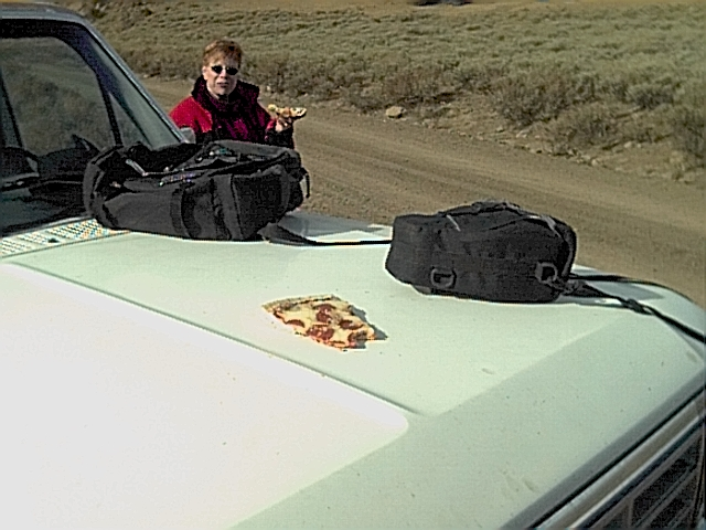 Cold pizza warming on the hood of the truck.