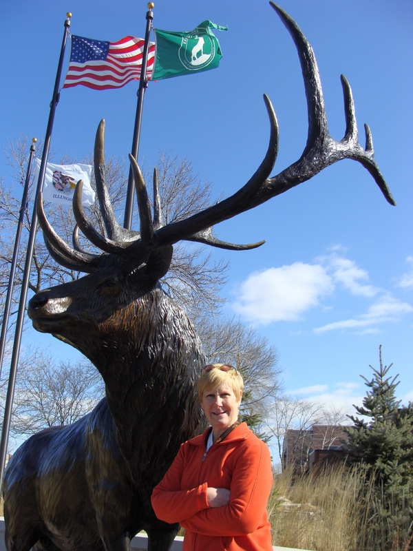 Cynthia poses at the namesake of Elk Grove Village