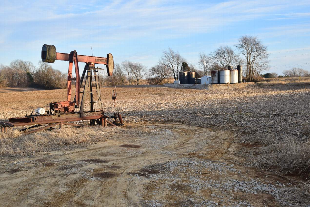 Oil production activity in this area, a oil well pump in front and an oil gathering facility at background
