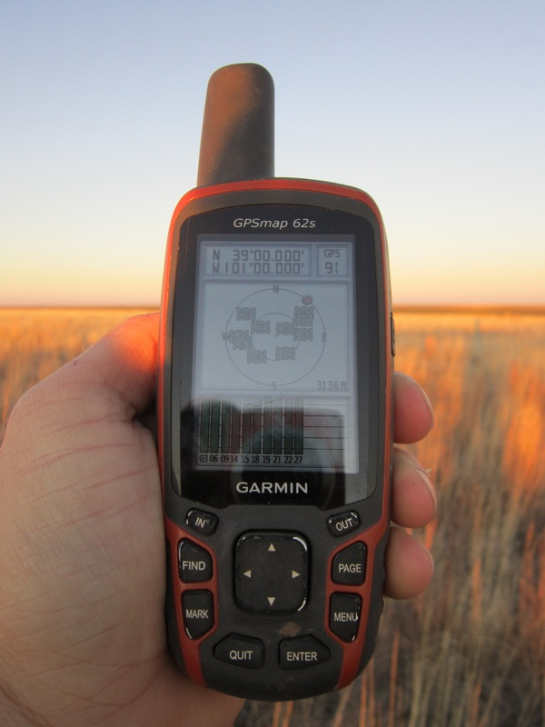 GPS at confluence point, showing elevation and accuracy, as well ground cover in the background.