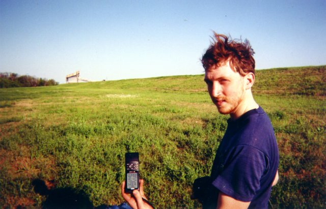 Alex holds the GPS, with a view to the east in the background.