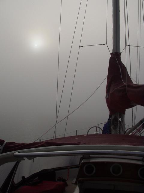 The sun peeks through the thick fog while underway