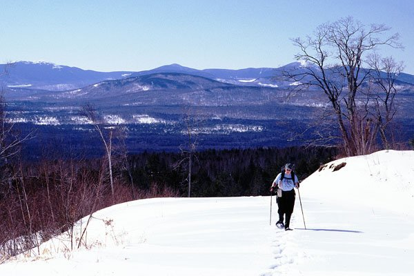 Snowshoeing over the crest of a hill with the Western Mountains in the background