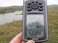 #6: Wet GPS at the confluence point with the reservoir in the background.