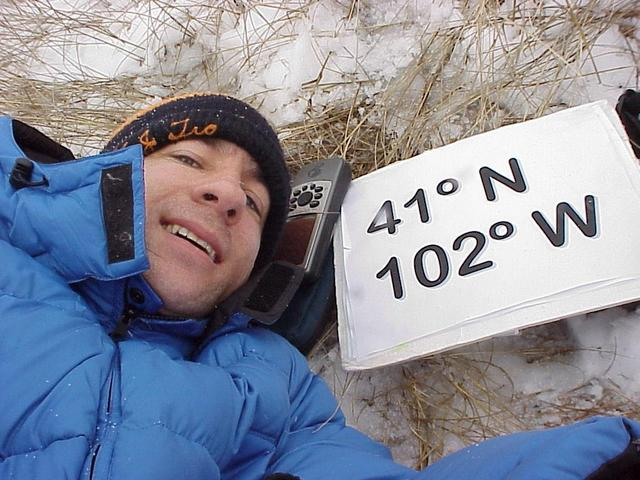 Geographer Joseph Kerski lying on the grass and snow at the confluence site.