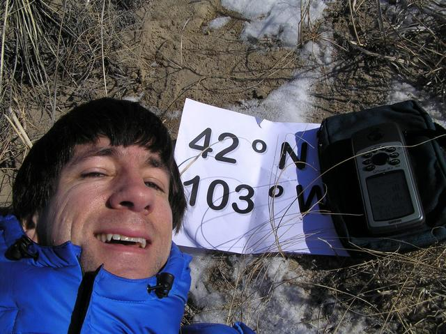 Joseph Kerski lying in the sand hills on the confluence of 42 North 103 West.