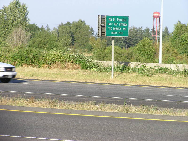 The confluence point lies on this freeway on-ramp, in front of this car.  A sign notes the 45th parallel