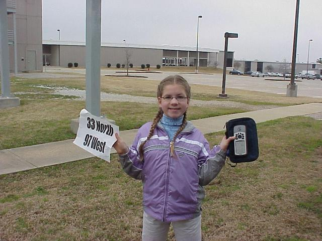 Emily Grace Kerski at the confluence site, GPS and sign in hand.