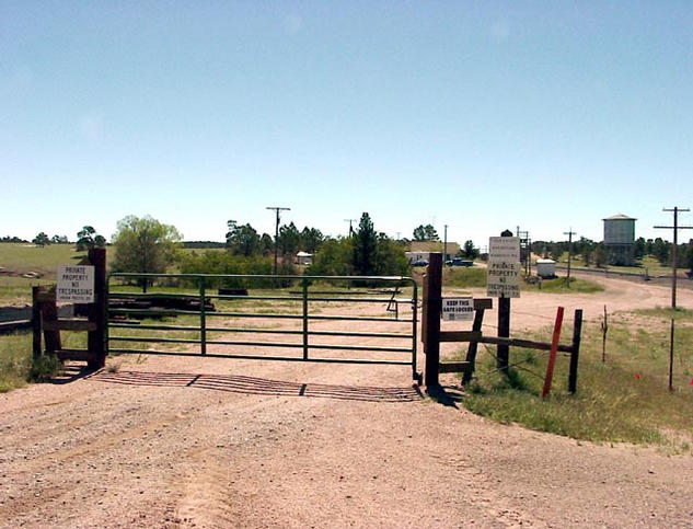 The gate blocking the dirt road along the Union Pacific railroad tracks.