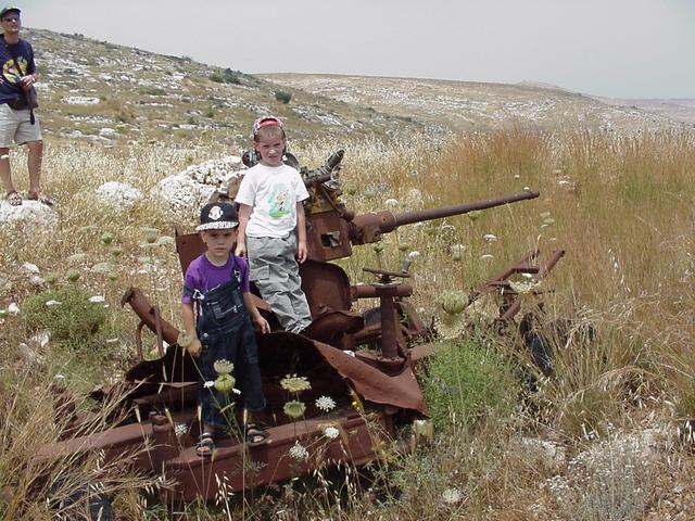 Tal and Omer sitting on an old cannon, Tsvika on the left